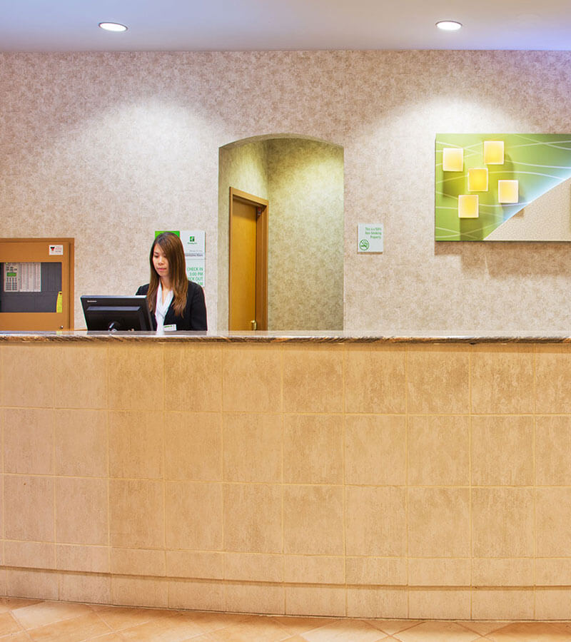An employee behind the check-in desk at the Holiday Inn North Vancouver