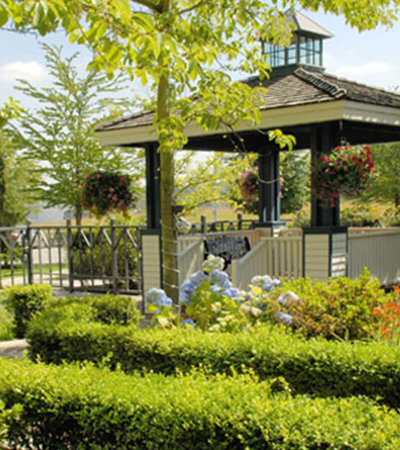 Gazebo amidst trees, flowers and manicured shrubs