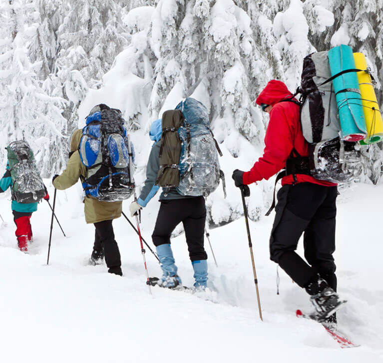 Skiers hiking up a snowy trail