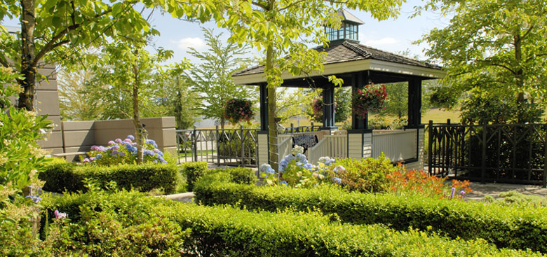 Gazebo surrounded by green trees and manicured shrubs