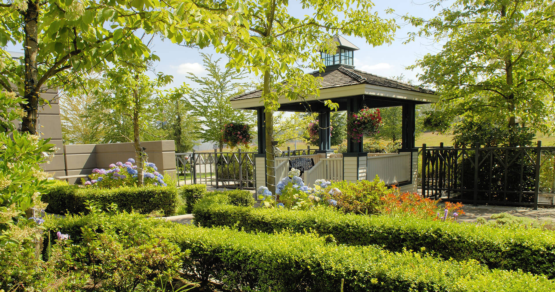 Gazebo nestled among flowers, manicured trees and shrubs