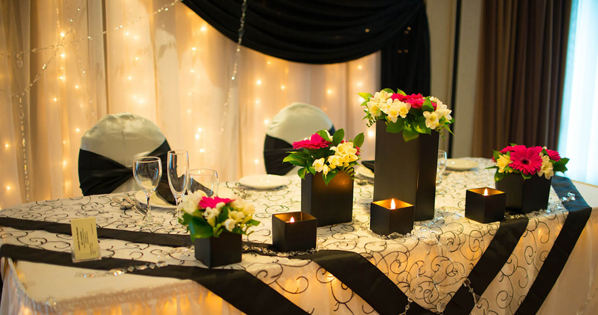 Dining table set in black and white theme with flowers and candles