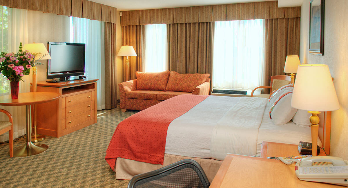 Single bed room with multiple windows letting in lots of natural light at Holiday Inn North Vancouver