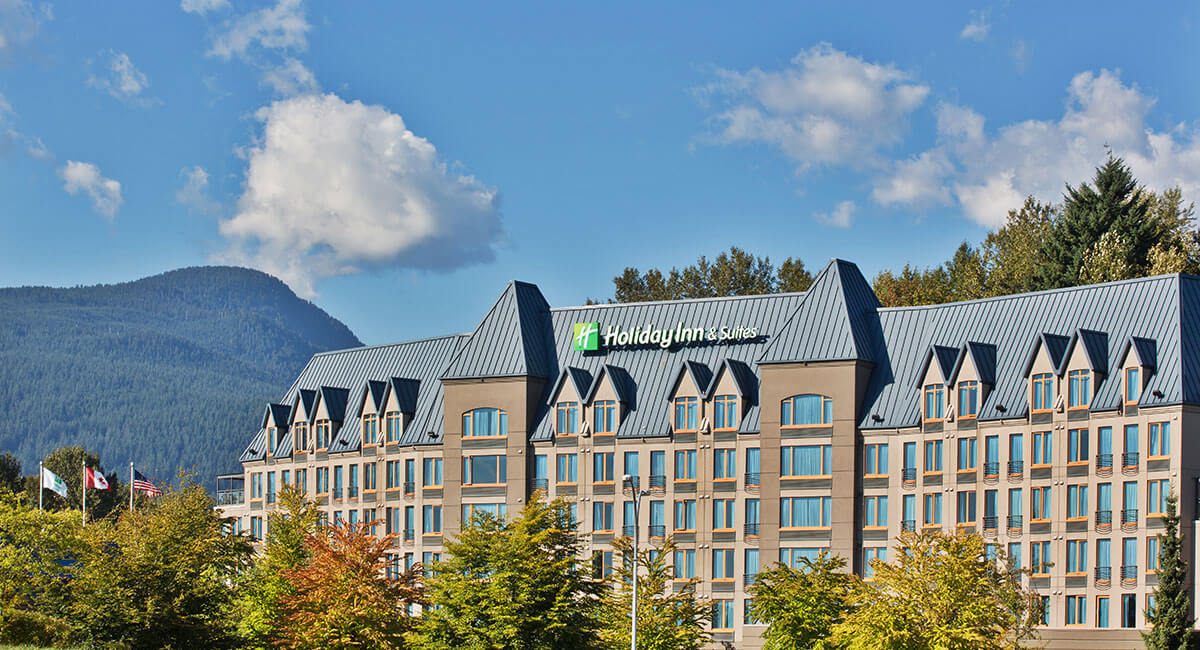 Holiday Inn North Vancouver against the backdrop of blue sky, mountains and trees
