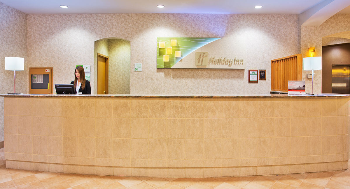 An employee overseeing the check-in desk at the Holiday Inn North Vancouver