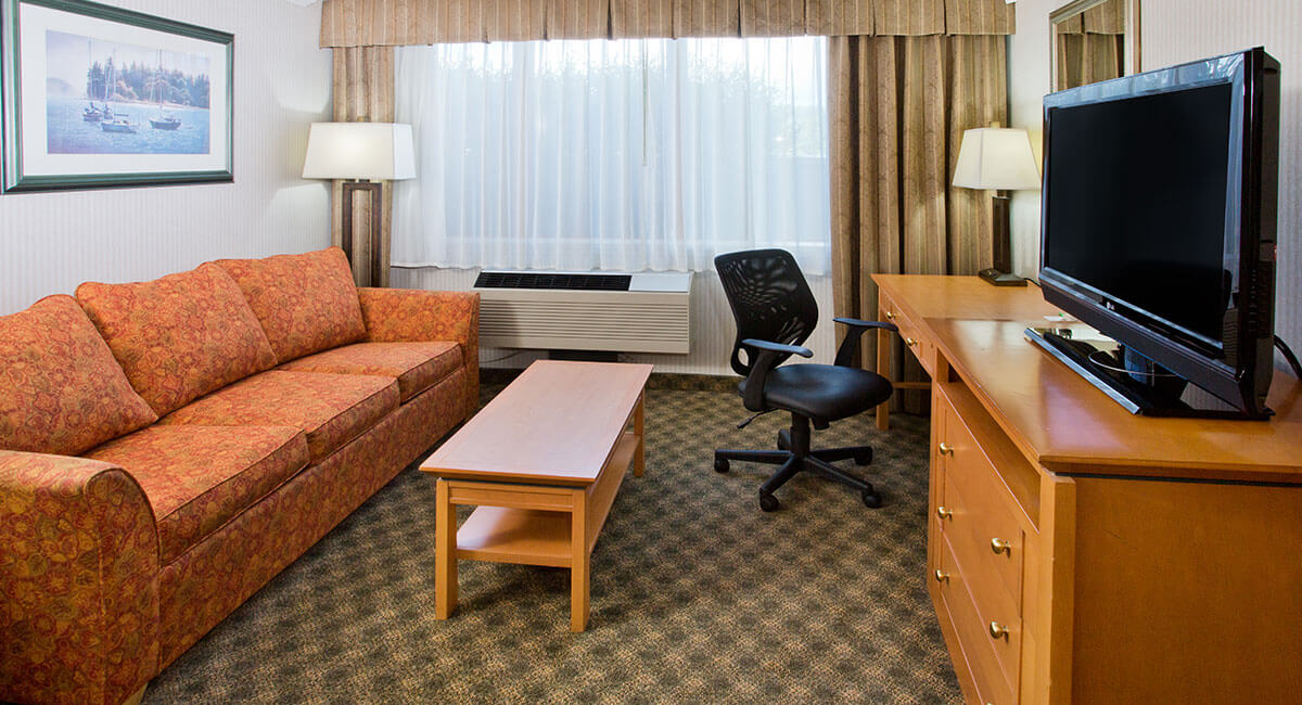 Room with spacious couch, desk, coffee table and TV at Holiday Inn North Vancouver