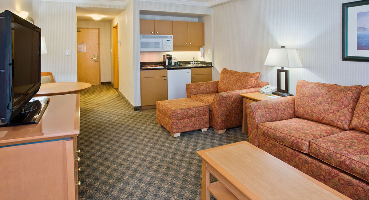 A sitting room with sofas, a table and kitchenette at the Holiday Inn North Vancouver