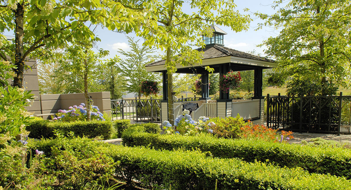 Gazebo surrounded by flowers and trees in the sunshine at Holiday Inn North Vancouver