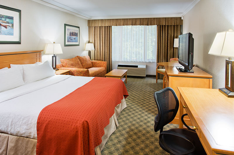 Single queen room with desk, nightables and sofa at the Holiday Inn North Vancouver