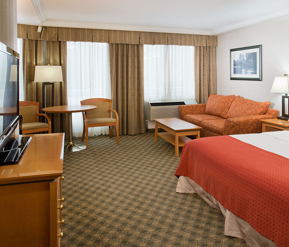 Single queen room furnished with tables, lamps and chairs at the Holiday Inn North Vancouver