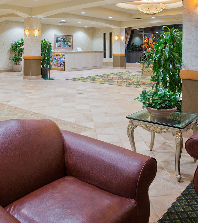 Elegant hotel lobby with leather couches and plants at the Holiday Inn North Vancouver