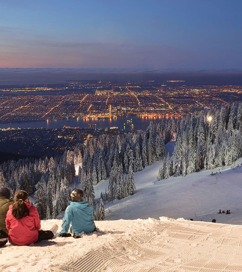 People sitting atop a snowy mountain peak overlooking trees and city lights of Vancouver
