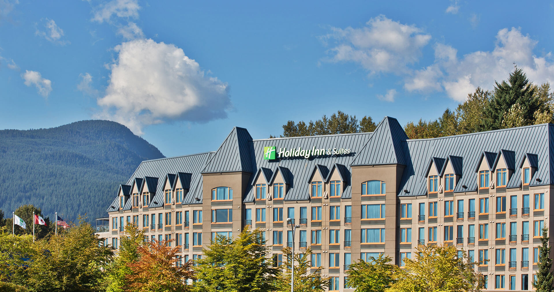 Holiday Inn North Vancouver surrounded by blue skies, trees and mountains