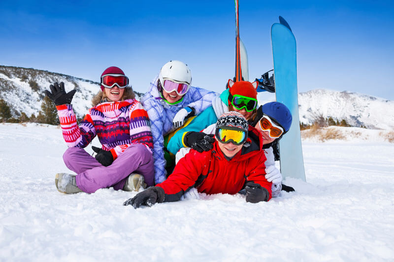 Five people enjoying the snow and skiing